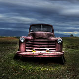 Old Automobile. An old red car sitting in a nice open grass field Royalty Free Stock Photography