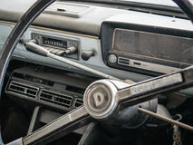 Old automobile interior with dashboard and big wheel Stock Photo