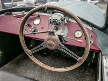 Old automobile interior with dashboard and big wheel. Dashboard of old car with big wheel, nostalgia for a time which has passed, old automobile interior Stock Image