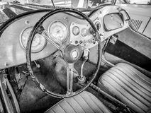 Old automobile interior with dashboard and big wheel. Dashboard of old car with big wheel, nostalgia for a time which has passed, old automobile interior Royalty Free Stock Image