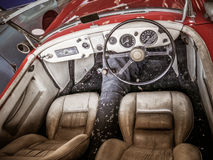 Old automobile interior with dashboard and big wheel. Dashboard of old car with big wheel, nostalgia for a time which has passed, old automobile interior Stock Images