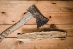 Old ax and chipped branch. On a wooden table Royalty Free Stock Image