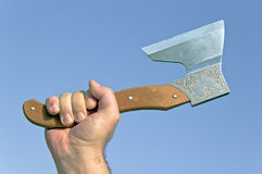 Old ax in hand. Over blue sky Stock Images