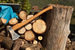 Old ax on log and firewood. Axe Cut into Wood after Chopping Firewood. Stock Images