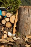 Old ax on log and firewood. Axe Cut into Wood after Chopping Firewood. Royalty Free Stock Photo