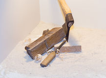 Old ax, plane, chisel and wood shavings on a light background.  royalty free stock images