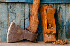 Old ax, planer and shavings on a blue wooden background.  Stock Photos