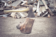 The old ax is stuck in an old log on the background of wooden firewood lying on the ground. Stock Photo