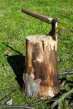 Old ax stuck in a wooden log Royalty Free Stock Image