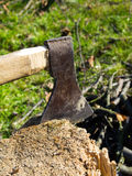 Old ax stuck in a wooden log Stock Images