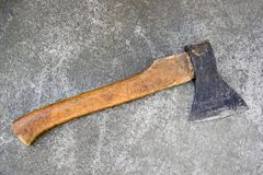 Old ax with a wooden handle lying on the concrete floor. royalty free stock photos