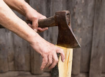 The old axe in the hands of an elderly person colitis firewood. The old axe in the hands of an elderly person colitis firewood Royalty Free Stock Photography