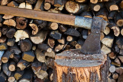 Old axe in log on a firewood background Stock Photo
