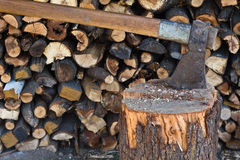Old axe in log on a firewood background Royalty Free Stock Images