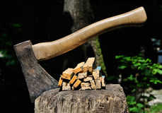 Old Axe stuck in a chopping block with splinters Royalty Free Stock Photography