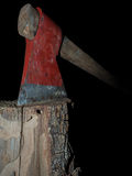 Old axe stuck in log isolated over black Royalty Free Stock Image