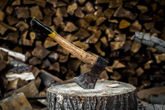 The old axe stuck in a stump. On a background of chopped firewood Royalty Free Stock Photo