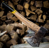 The old axe stuck in a stump. On a background of chopped firewood Stock Photos
