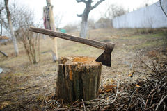 Old axe in stump. Old thrown garden. Dry grass. Autumn sad landscape Stock Photography