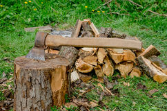 Old axe in wood. Old axe in stump and firewood on grass Stock Image