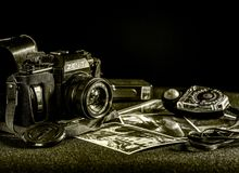 Old b/w camera on a table with pictures and old lightmeter. An old camera on a table with pictures and old lightmeter black and white Royalty Free Stock Photos