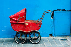 An old baby carriage against a blue wall Royalty Free Stock Image