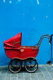 An old baby carriage against a blue wall Royalty Free Stock Photography