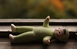 Old baby-doll lying on the window-sill Stock Images