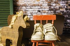 Old Baby Shoes and Antique Cradle. Worn baby shoes on small red rocking chair next to wooden toy horse and antique cradle with green shutter and brick wall stock images