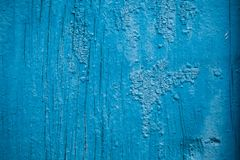 Old background of cracked paint of blue color on a wooden surface royalty free stock photography