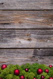 Old background of wood with red xmas balls and moss. Stock Image