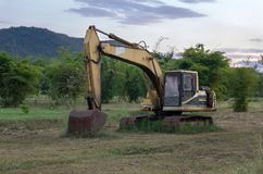 Old backhoe on construction site in the green fields. With sunset Royalty Free Stock Images