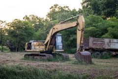 Old backhoe on construction site. In the green fields Royalty Free Stock Image