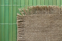 Old   backing of burlap on the green bamboo  mat Stock Photography