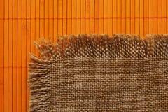 Old  backing of burlap on the orange bamboo  mat Royalty Free Stock Photo