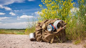 Old backpack with map compass on rural road Stock Photography