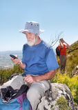 Old backpacker sending sms sitting on rock Royalty Free Stock Photos