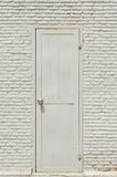 Old back door. Old bacldoor with the white wall background Royalty Free Stock Image