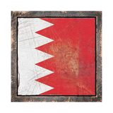 Old Bahrain flag. 3d rendering of a Bahrain flag over a rusty metallic plate wit a rusty frame. Isolated on white background Stock Images