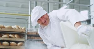 Old baker chef in a bakery industry preparing the dough he unloaded the flour in a industrial container while looking. Straight to the camera and smiling cute stock video