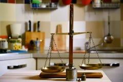 Old balance on wooden table on kitchen  background. Old brass balance on wooden table on kitchen  background Stock Photo