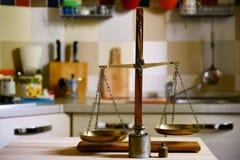 Old balance on wooden table on kitchen  background. Old brass balance on wooden table on kitchen  background Stock Photos