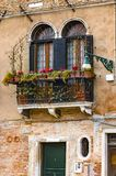 Old balconies in a Venice colorful building with red flowers Royalty Free Stock Photo