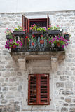 Old balcony with flowers and window with shutters Stock Images