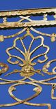 Old balcony railing, with filigree ornaments, and face gold. Old balcony railing, with filigree ornaments, and face, and a shell in gold stock photography