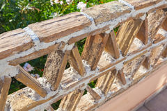 Old balcony railings made of clay blocks. Greek style architecture details, close up Royalty Free Stock Photo