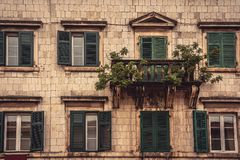 Old balcony with trees and flowers on old medieval building facade with windows in medieval architecture in ancient European city Royalty Free Stock Photos