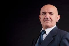 Old bald businessman. Old bald self-confident businessman on a dark background Royalty Free Stock Image
