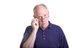 Old Bald Guy in Blue Shirt Pulling Down Glasses Stock Photography