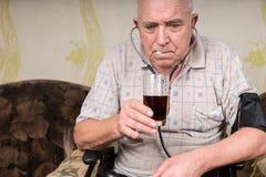 Old Bald Man with BP Apparatus Taking his Medicine Stock Photos